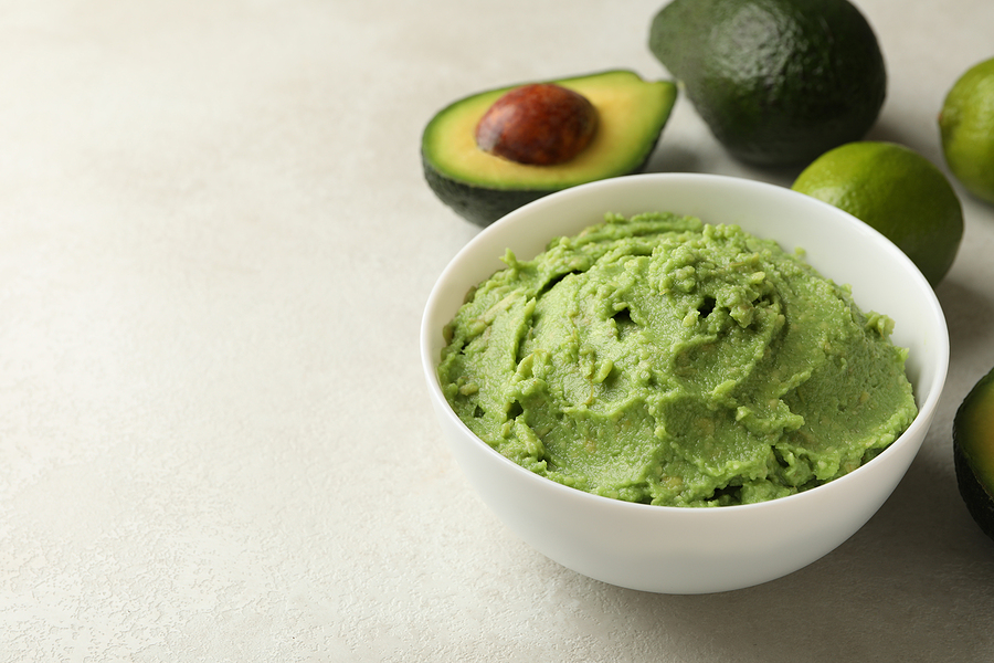 Bowl of guacamole, avocado and lime on white textured background, space for text